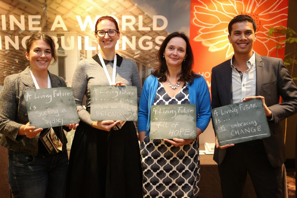 Attendees stand with ILFI CEO Amanda Sturgeon (second from right) and advertise their own visions for a Living Future. Photo by Danielle Barnum.
